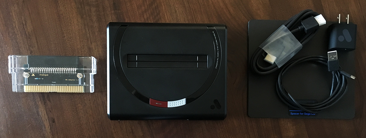 The Mega Sg comes with a Master System cartridge adapter, HDMI cable, Micro USB cable, power adapter, and a Sega CD spacer mat.