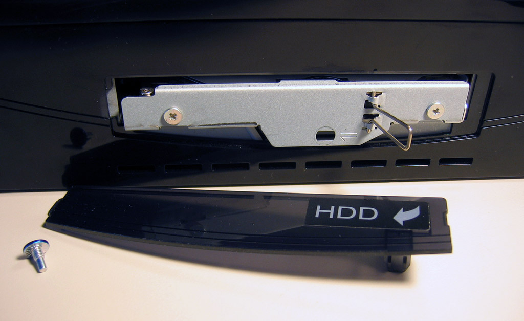 Open the metal latch, move the drive tray to the right, and slide out the drive.