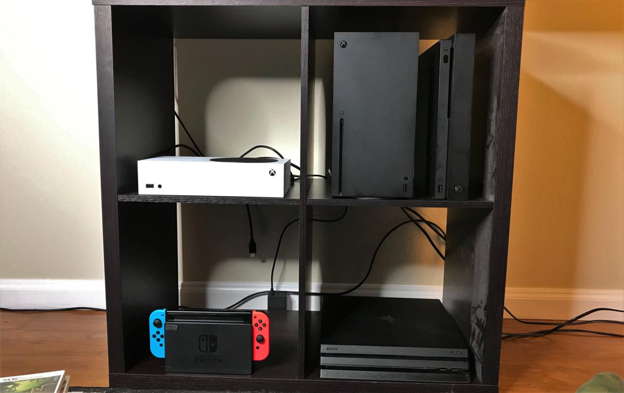 The Xbox Series S (top left) and Series X (top right) alongside the three current-gen consoles in a poor person (me) TV stand.